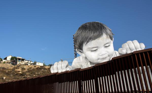 The work built by French artist JR peers over the U.S.-Mexico border at Tecate, Calif., earlier this week.