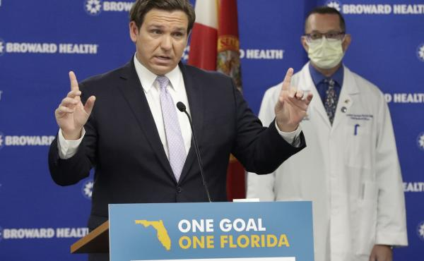 Florida Gov. Ron DeSantis, left, speaks during a news conference along with Dr. Joshua Lenchus, chief medical officer of Broward Health Medical Center on Monday. The number of patients in Florida hospitals for COVID-19 was relatively stable, at just below