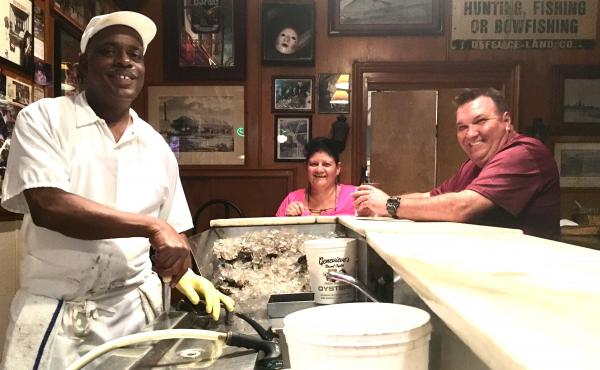 """Thomas """"Uptown T"""" Stewart (left), has been shucking oysters at Pascal's Manale restaurant for more than 30 years, about as long as Paula (middle) and Brent Coussou have been going there."""