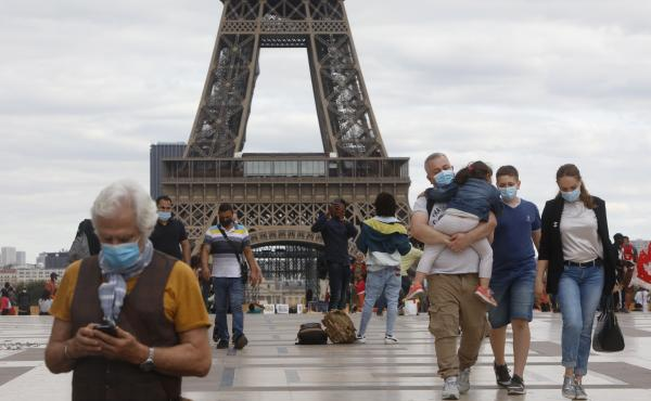 People wearing masks walk near the Eiffel Tower in Paris on Thursday, the same day that the government made masks mandatory in all the city's public outdoor spaces.
