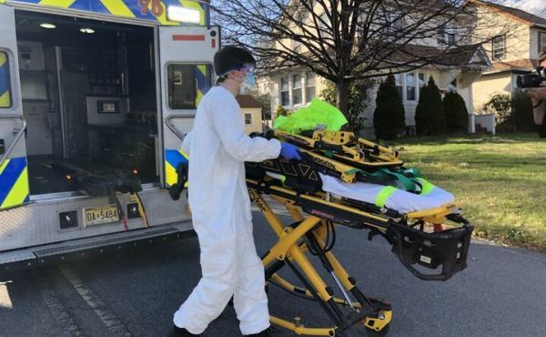 Teaneck Volunteer Ambulance Corps member Bobby Alexiou, 20, wheels out a stretcher outside the home of a potential COVID-19-positive patient in Teaneck, N.J., after suiting up in a protective suit, donated goggles from the local high school and an N95 mas