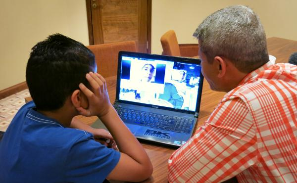 Palestinian Imad Abudayyah and his son, Ghassan, speak to relatives in the Gaza Strip via Skype from Ramallah in the West Bank. Israeli restrictions make it extremely difficult to travel between the two territories. West Bank Palestinians have largely bee
