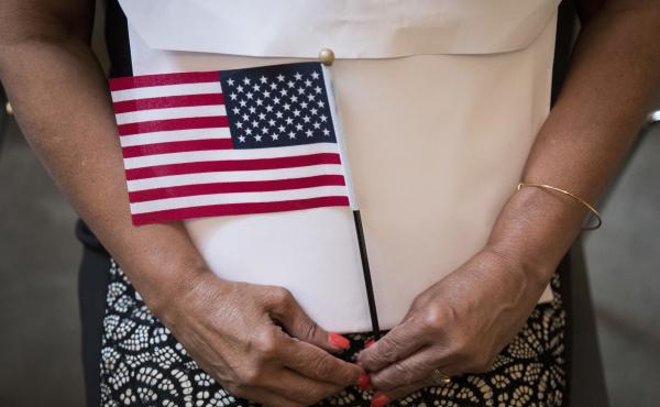 A participant in a 2018 naturalization ceremony holds a U.S. flag in New York City. Research by the Census Bureau suggests the citizenship question is highly likely to scare households with noncitizens from taking part in the constitutionally mandated hea