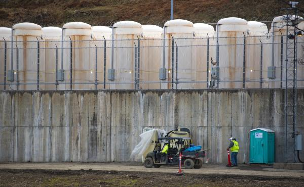 Once it is safe to remove the spent fuel from the pool, it's stored outside in metal casks. They are lined up on a concrete base, behind razor wire and against a hillside near the power plant.