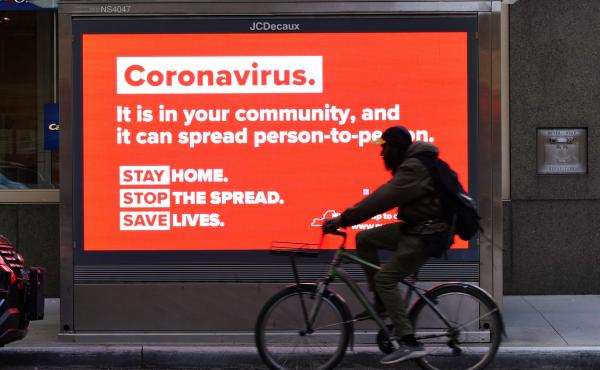 A person on a bike rides by a sign in New York City urging people to stay home in May. As the pandemic drags on, some workers are facing tough choices — balancing potential risks of unwittingly spreading the disease against the possibility of losing pay