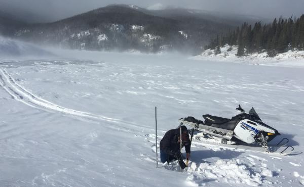 Reservoir caretaker Doug Billingsley tests water levels at windswept Chambers Lake near Cameron Pass, Colo.