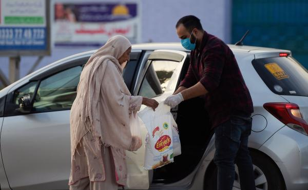 A man donates food to an elderly woman during a government-imposed nationwide lockdown as a preventive measure against the new coronavirus in Islamabad on Sunday.