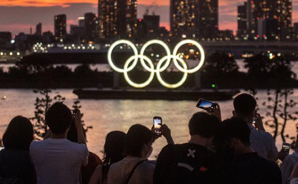 People take pictures as the Olympic rings lit up at dusk on the Odaiba waterfront in Tokyo on Thursday, the eve of the official start of the Tokyo 2020 Olympic Games.