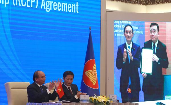 Vietnamese Prime Minister Nguyen Xuan Phuc (left) and Trade Minister Tran Tuan Anh applaud next to a screen showing Japanese Prime Minister Yoshihide Suga and Trade Minister Hiroshi Kajiyama holding up signed RCEP agreement, in Hanoi, Vietnam. China and 1