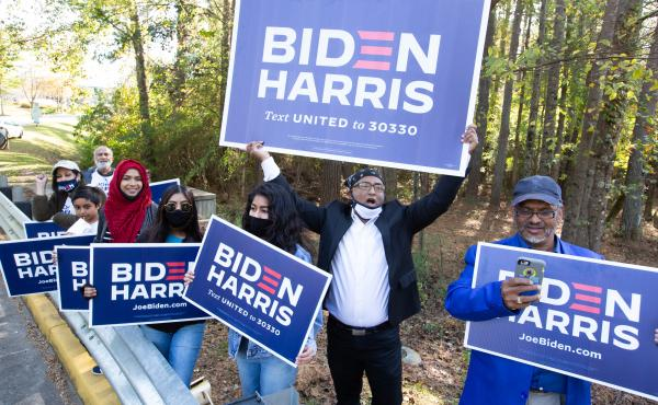 Voters wave Biden-Harris campaign signs at the entrance to a polling station in Gwinnett County, Ga., on Nov 3. Gwinnett is one of the five Atlanta metro counties that saw a dramatic increase in turnout among Asian American and Pacific Island voters this