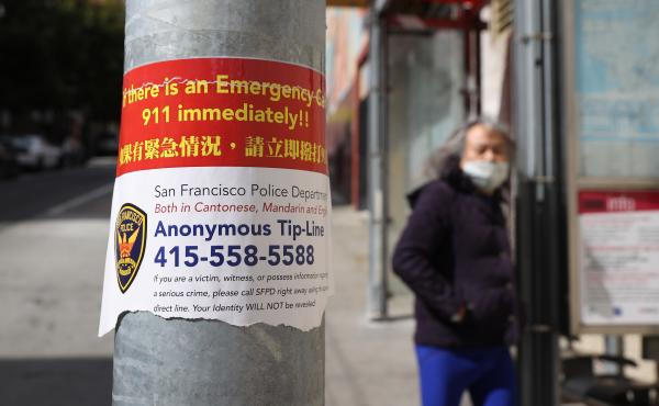 A sign posted in San Francisco's Chinatown neighborhood on March 8 encourages people to call a police tip line if they witness a crime.