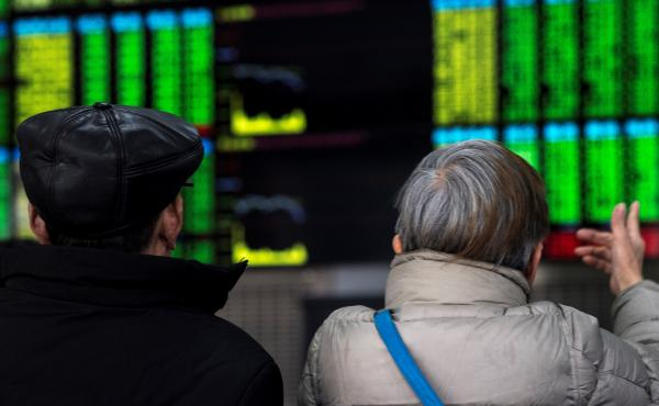 Two investors chat while keeping an eye on stock price movements shown on a screen at a securities company in Shanghai on Friday.