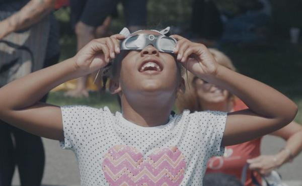 A child in Charlottesville, Va., uses eclipse glasses to safely watch the August 2017 solar eclipse.