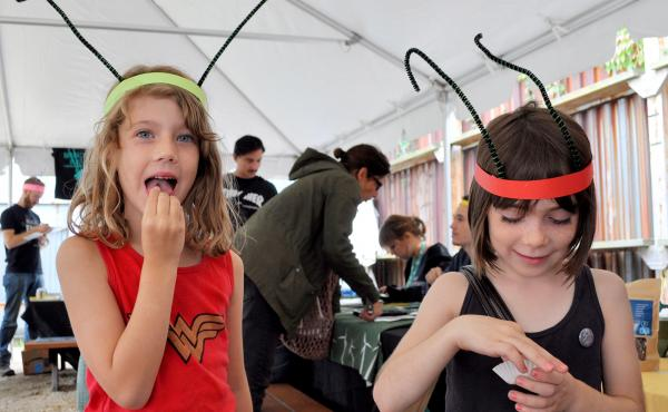 """Tennesee Nydegger-Sandidge (left) and Holly Hook try chowing down on some crickets. """"People should eat them because they're good for the planet,"""" says Tennessee."""
