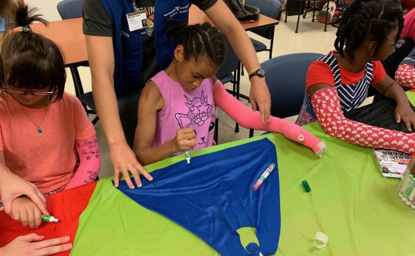 """At Nashville's """"High Five"""" camp, 12-year-old Priceless Garinger (center), whose right side has been weakened by cerebral palsy, wears a full-length, bright pink cast on her left arm — though that arm's strong and healthy. By using her weaker right arm a"""