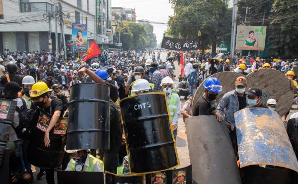 Demonstrators take shelter and block the road during a protest against the military coup in Mandalay, Myanmar on Wednesday.