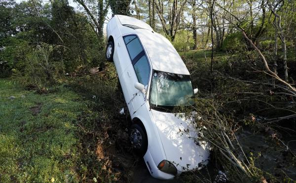 A car that was carried by floodwaters leans against a tree in a creek in Nashville, Tenn., on Sunday. Heavy rainfall flooded roads, submerged vehicles and left many people in need of rescue.