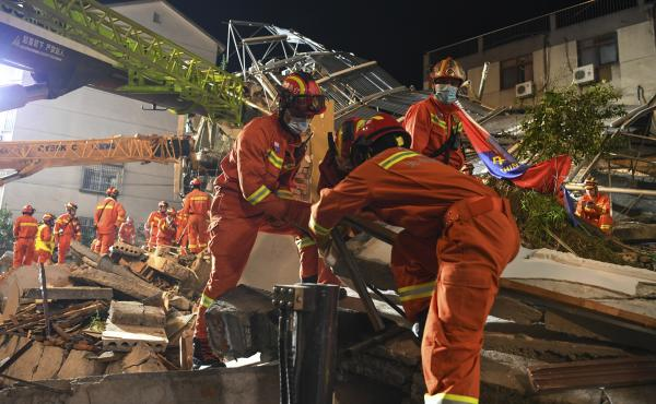 In this photo released by Xinhua News Agency, rescuers prepare equipment as they search for survivors at a collapsed hotel in Suzhou in eastern China's Jiangsu Province on Monday.
