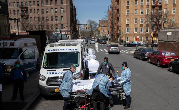 Paramedics and hospital workers prepare to lift a COVID-19 patient onto a hospital stretcher outside the Montefiore Medical Center Moses Campus in the Bronx, Tuesday, April 07, 2020, New York City.