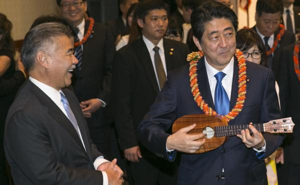 Japanese Prime Minister Shinzo Abe (right), strums a pineapple-shaped ukulele presented to him by Hawaii Gov. David Ige at a dinner on Monday in Honolulu. Abe and President Obama visited Pearl Harbor on Tuesday, 75 years after the surprise Japanese attack