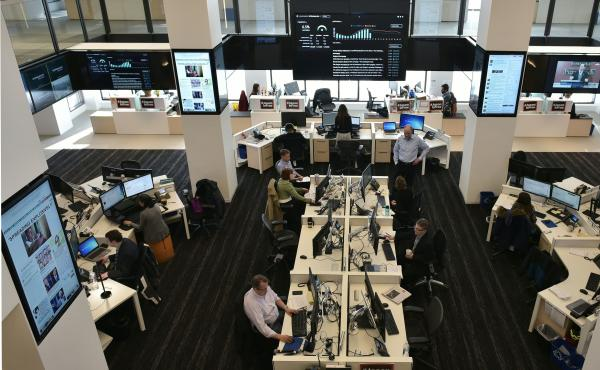 Journalists at The Washington Post work in a newsroom surrounded by screens showing its website and updated reader metrics.