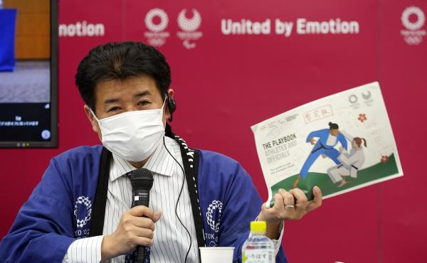 Tokyo Games Delivery Officer Hidemasa Nakamura holds a sample of an updated version of the playbook during a news briefing on Wednesday.