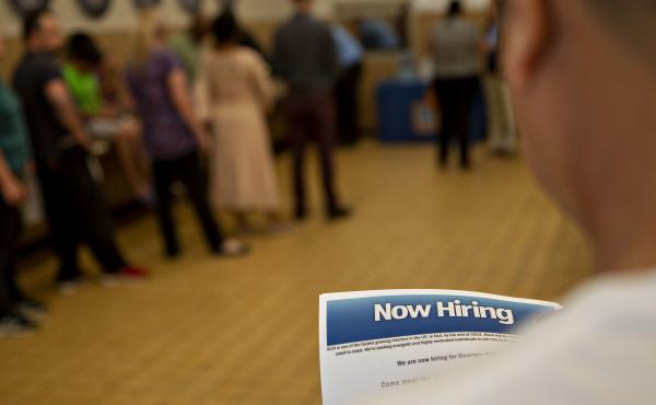 The U.S. has added jobs in every month for nearly eight years. Here, a job seeker holds an employment flyer during a hiring event at an Aldi Supermarket in Darien, Ill., in July.
