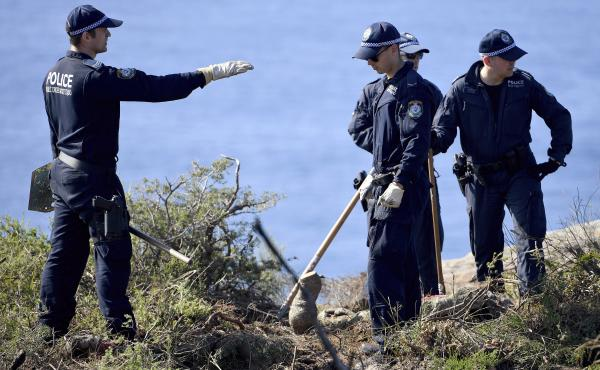 Police search a headland in Sydney, Australia, on Tuesday, following an arrest in relation to the death of a man in 1998. More than 30 years after Scott Johnson died after falling off a cliff in Sydney, authorities have charged a man with his death, in an