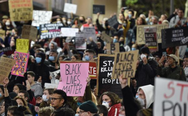 "Marchers shout slogans and hold up placards Tuesday during a ""rally for justice"" in Sydney, protesting the deaths of members of the Aboriginal community in Australia and the death of George Floyd, an unarmed black man who died in police custody in Minneap"