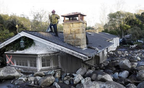 A firefighter stands on the roof of a house submerged in mud and rocks Wednesday in Montecito, Calif.