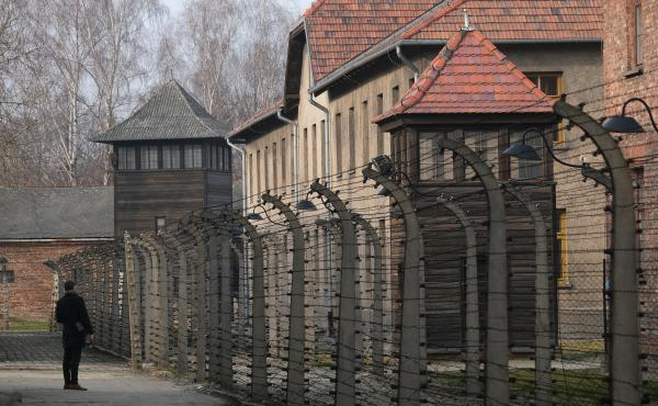 A visitor walks near barbed wire and prison barracks at the former Auschwitz I concentration camp on Jan. 26, 2020, in Oswiecim, Poland.