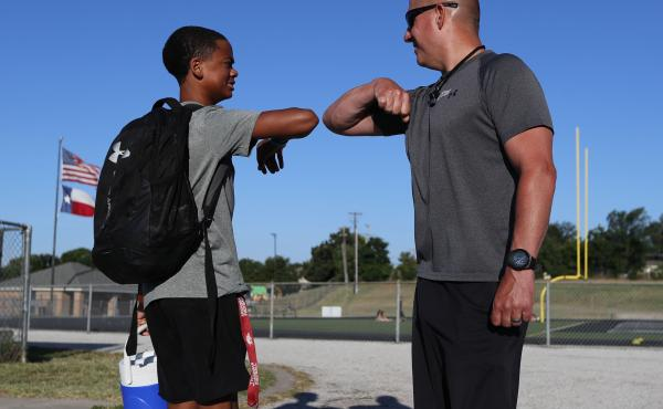 Football coach Bob Wager (right) and sophomore safety Cameron Conley greet each other Thursday at the reopening of strength and conditioning camp at Martin High School in Arlington, Texas. State officials say they plan to open schools for in-person instru