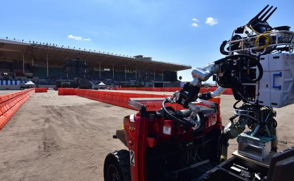 MIT's Atlas robot, nicknamed Helios, completes the driving task at the June 2015 DARPA Robotics Challenge Finals. Helios is a second-generation Atlas, developed for DARPA by Boston Dynamics.