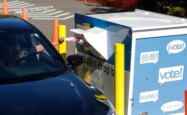 A voter inserts a ballot in a drive-up drop box last week in Renton, Wash., in that state's primary. With more states expanding absentee voting due to the pandemic, the use of drop boxes is growing and leading to legal challenges from some Republicans.