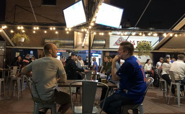 Sox fan Steve Nitz (left) and Cubs fan Paul Schmitz watch the crosstown rivals play each other last weekend in the beer garden at Bernie's Tap and Grill across the street from Wrigley Field in Chicago.