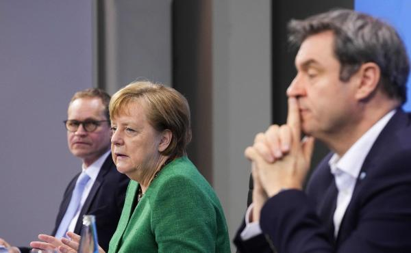 German Chancellor Angela Merkel, with Bavaria's State Premier Markus Soeder (right) and Berlin's Mayor Michael Mueller, participate in a news conference following talks via videoconference with Germany's state premiers on the extension of the current COVI