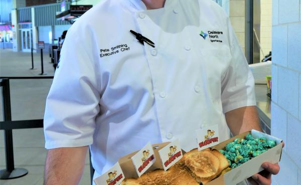 Chef Pete Smithing holds the Blooper Burger, which includes pretty much all the concession stand foods you can think of, at SunTrust Park in Georgia. For dessert: caramel popcorn colored with the Atlanta Braves' red and blue.