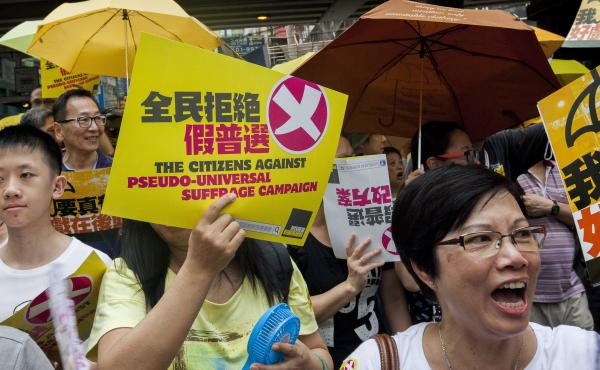 Supporters of free and open elections in Hong Kong march through the city streets ahead of a crucial vote on political reform in the city's Legislative Council.