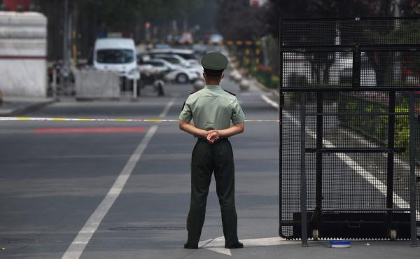 A law enforcement officer stands guard at the entrance of the Xinfadi market Saturday in Beijing. A fresh cluster of coronavirus cases linked to the market prompted officials to institute immediate and sweeping restrictions, including the market's closure