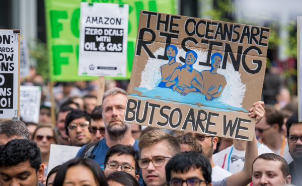 """A protester holds a sign reading """"The Oceans Are Rising But So Are We"""" at an Amazon employee walkout in Seattle, as part of the Global Climate Strike on Sept. 20, 2019. At some companies, employees are putting increasing pressure on their bosses to act on"""