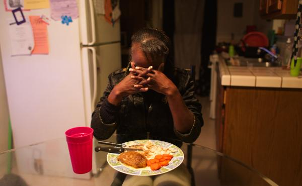Erica Johnson prays before her meal. She volunteers at the food pantry at John Still school where three of her four children are students. She eats alone after she feeds her kids.