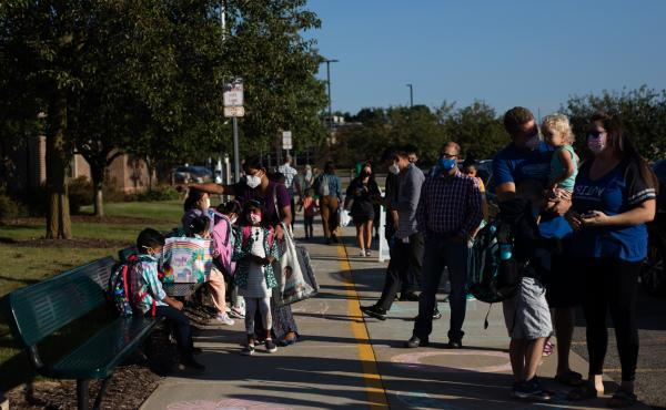 Parents drop their children off for the first day of school in Novi, Mich., on Tuesday.