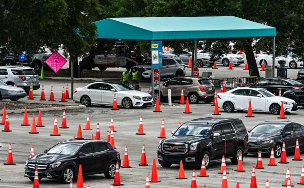 People wait in their vehicles to get vaccinated last week at a drive-through site at Hard Rock Stadium in Miami Gardens, Fla. President Biden announced an April 19 deadline for all states to open eligibility to individuals ages 18 and up.