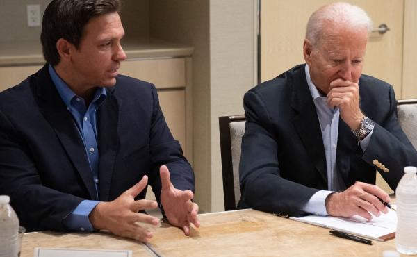 President Biden listens Thursday as Florida Gov. Ron DeSantis discusses the collapse of the 12-story Champlain Towers South condo building in Surfside, Fla.