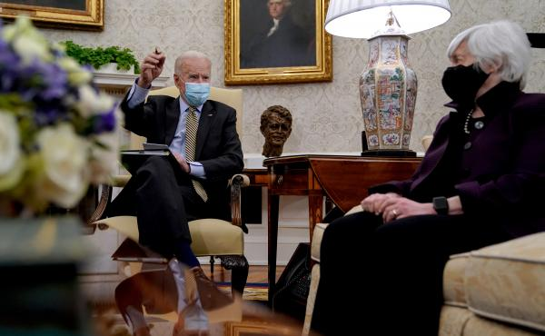 President Biden speaks as Treasury Secretary Janet Yellen listens during the weekly economic briefing in the Oval Office at the White House on April 9. Biden issued an executive order compelling Yellen and other regulators to assess the risk of climate ch