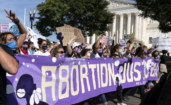 Thousands of demonstrators march outside the U.S. Supreme Court during the Women's March in Washington, Saturday, Oct. 2, 2021.