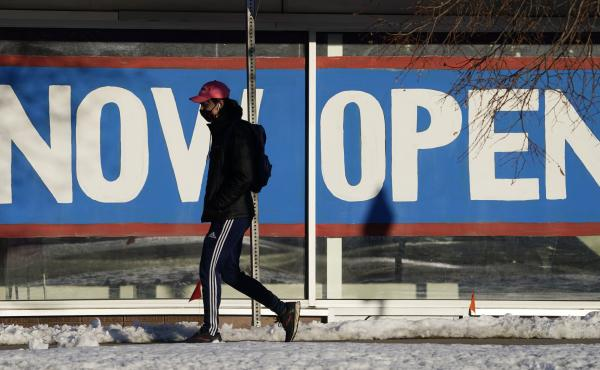 A pedestrian on Feb. 25 walks past the window of a restaurant with a sign promoting its re-opening in Boulder, Colo. Congress on Wednesday passed a $1.9 trillion stimulus plan, which is expected to provide a strong boost to economic growth.