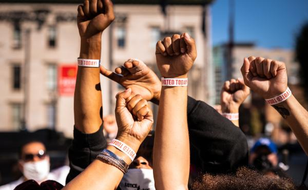 """Black Lives Matter protesters display wristbands reading """"I Voted"""" after leaving a polling place this month in Louisville, Ky. Activists warn Black and Latino voters are being flooded with disinformation intended to suppress turnout in the election's fina"""