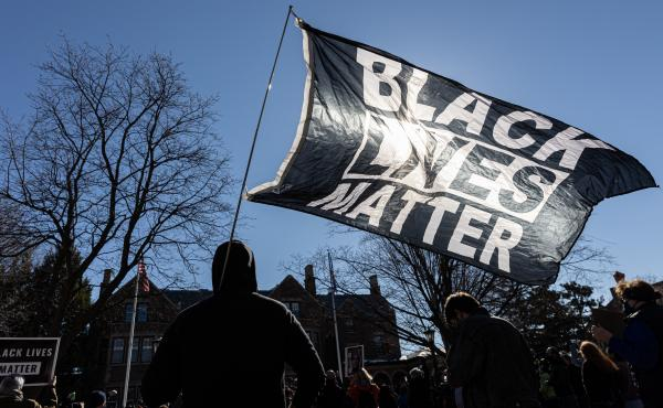A man holds a Black Lives Matter flag during a March protest in St. Paul, Minn. Support for Black Lives Matter surged after protests following George Floyd's death. Activists charge that disparaging posts targeting BLM are part of an overall effort to und