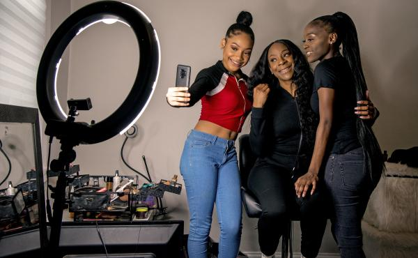Years ago, Portia Smith (center) suffered postpartum depression and feared seeking care because of child welfare involvement. She and her daughters Shanell Smith (right), 19, and Najai Jones Smith (left), 15, pose for a selfie after makeup artist Najai ma